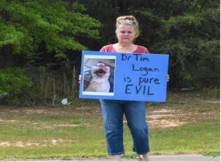 A protester stands outside of Andrews Avenue Animal Hospital in Ozark, Alabama, this week.